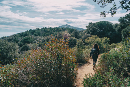 Woman walking in the distance on a trail among mountains