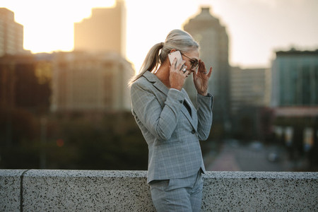 Senior businesswoman talking on phone on city bridge