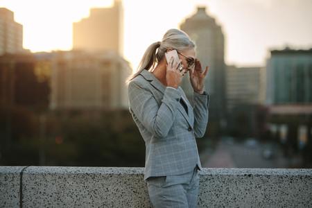 Senior businesswoman talking on phone on city bridge
