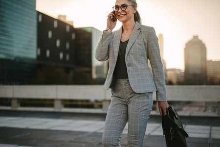 Businesswoman walking outdoors on city street with mobile phone