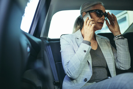 Senior female entrepreneur traveling to work in a luxury car