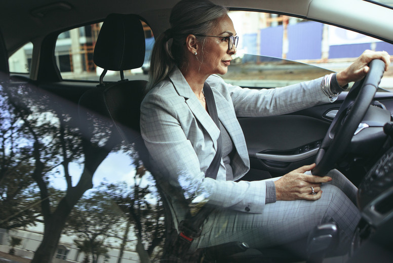 Senior businesswoman driving to office in a car