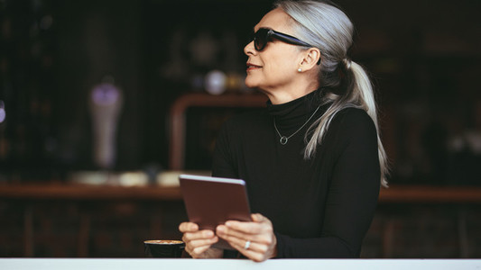 Mature woman at a coffee shop with tablet pc