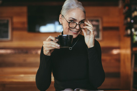 Charming senior woman at cafe having coffee