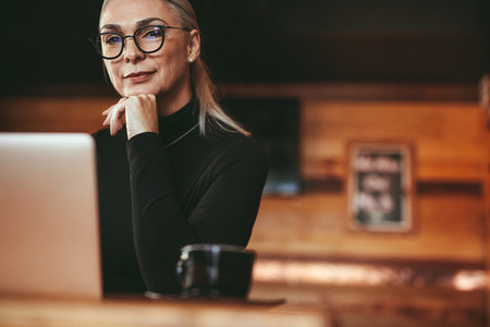 Beautiful mature woman sitting at cafe table with laptop