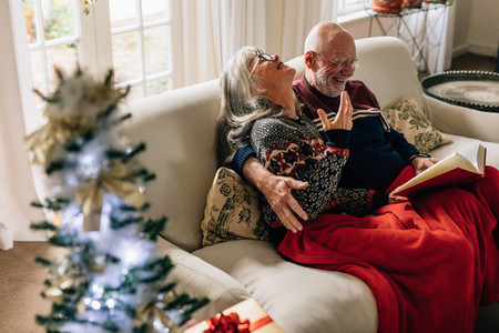 Elderly couple reading a book sitting on sofa at home