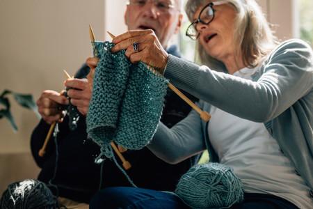 Senior couple knitting wool at home