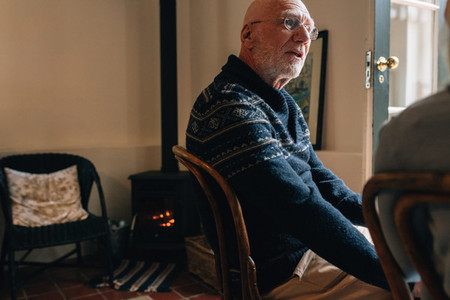 Senior man sitting on a chair at home and talking