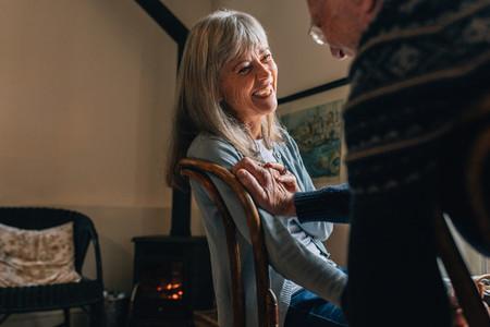Happy senior couple at home talking