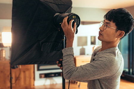 Photographer adjust softbox light intensity for shoot