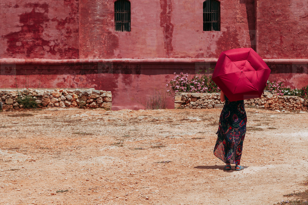 Young lonely woman with a red umbrella