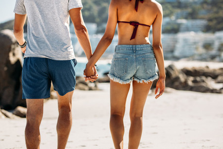 Rear view of a tourist couple walking on beach