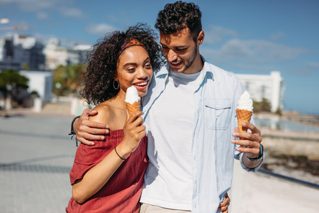 Romantic couple walking on street eating ice cream