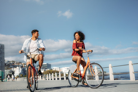 Tourist couple moving around the city on bicycles