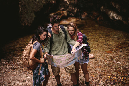 Friends using a map to find the route while hiking