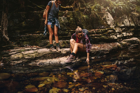 Female hikers by a water pond in mountain