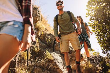 Friends hiking on rocky mountain trail