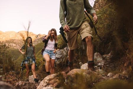 Group of friends walking through a mountain trail