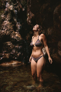 Female tourist in bikini inside a pond at forest