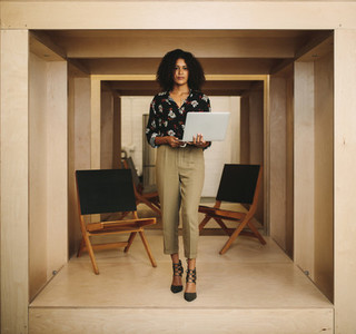Portrait of a businesswoman standing in office holding laptop