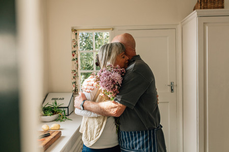 Senior couple embracing standing at home