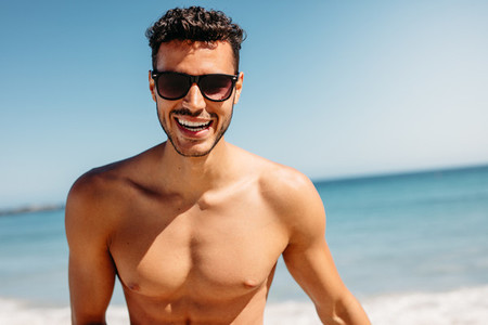 Close up of a shirtless man enjoying at the beach