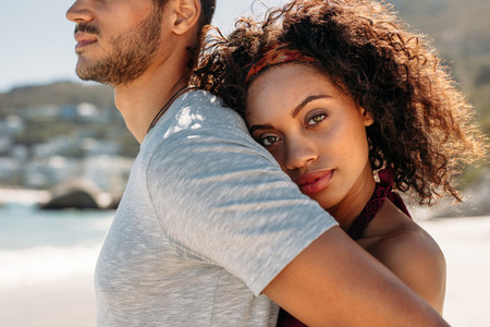 Close up of a woman standing behind a man embracing him
