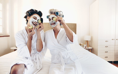 Happy women wearing beauty face pack sitting on bed holding slic