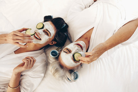 Top view of smiling mother and daughter lying on bed with face p