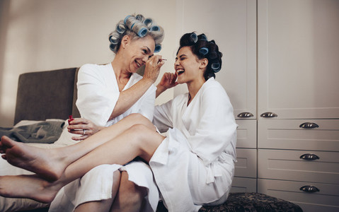 Mother and daughter in bathrobe having fun applying nail paint
