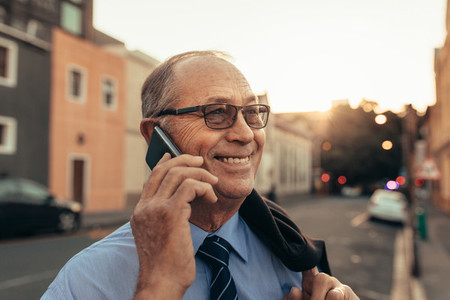 Senior businessman on city street using phone