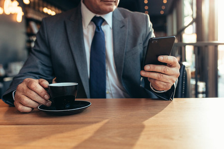 Smart phone in hand of a senior businessman at cafe