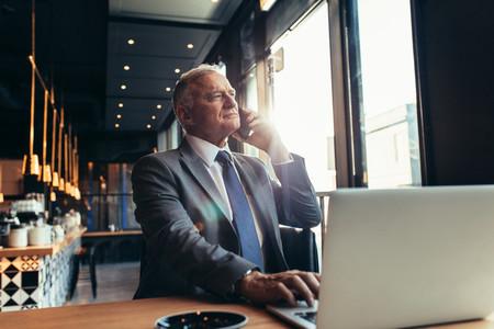 Senior businessman at coffee shop making a phone call