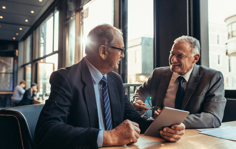 Two senior businessmen having an informal meeting at cafe