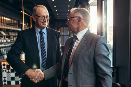 Business partners handshake at cafe