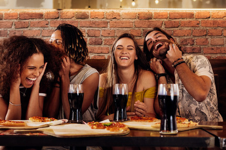 Cheerful young friends hanging out at restaurant