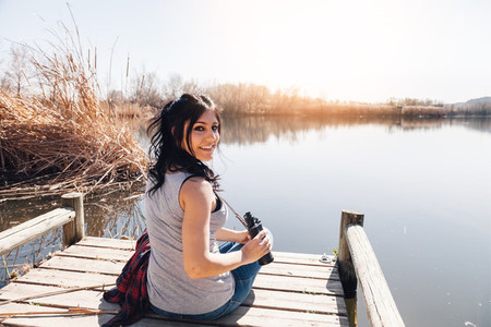 Young brunette woman sitting on a jetty with binoculars