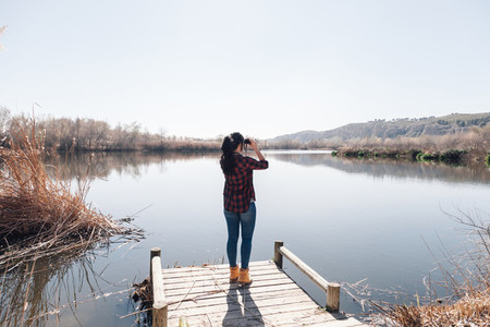 Young brunette woman on a jetty with binoculars