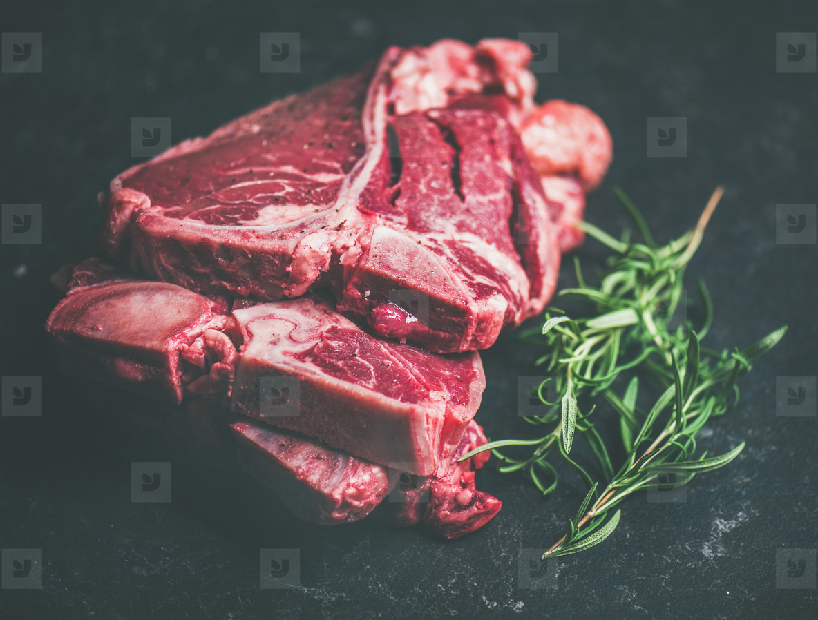 Raw beef meat t bone steaks with rosemary on black background
