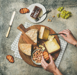 Cheese platter with female hands reaching to food  top view