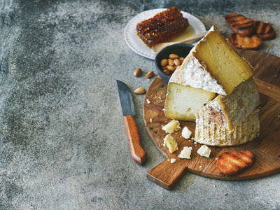 Cheese assortment and snacks on rustic wooden board  copy space