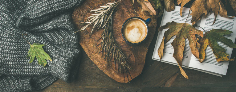 Fall morning coffee concept with fallen leaves  jamper and book