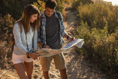Hiker couple using map on mountain trail