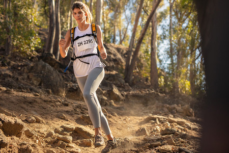 Female runner in extreme mountain race competition