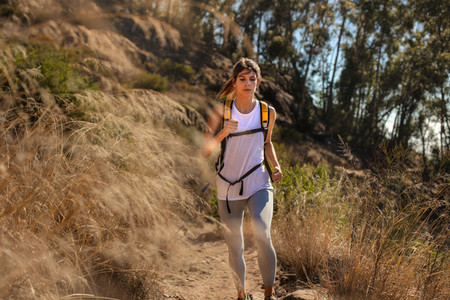 Fit woman running through mountain trail