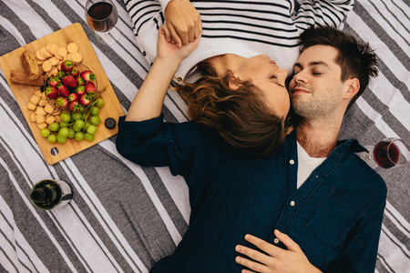 Romantic couple on date lying on floor with heads together