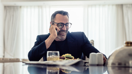 Businessman having lunch and talking on phone in hotel room