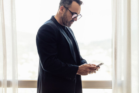 Businessman texting on mobile phone in hotel room