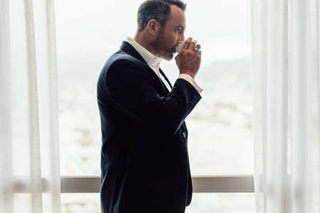 Business traveler in hotel room having coffee