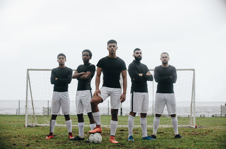 Soccer players standing in front of goalpost